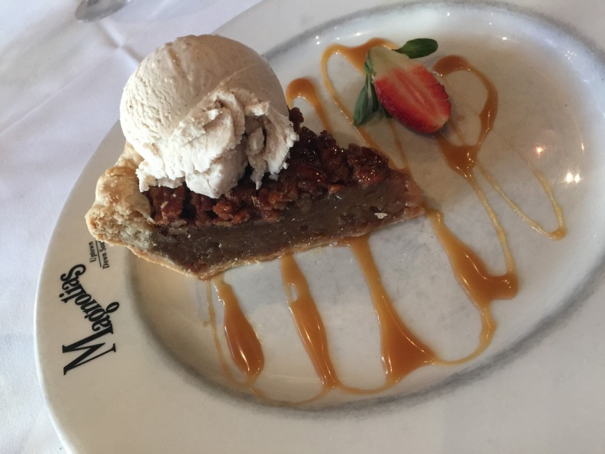 Southern pecan pie drizzled in bourbon caramel sauce and served with a scoop of vanilla bean ice cream